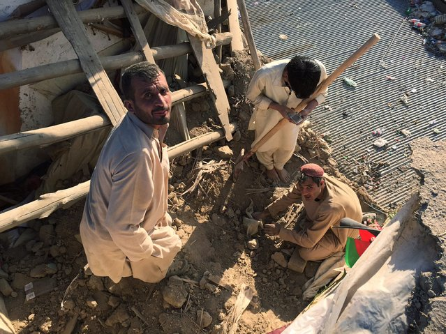 Afghans check the damage to the walls of their home after a 7.7 magnitude earthquake, in Kabul, Afghanistan, 26 October 2015. A 7.7 magnitude earthquake hit Pakistan and Afghanistan, killing at least 47 people and injuring hundreds in Pakistan, while 12 school girls were killed during a stampede following earthquake in Takhar, Afghanistan. (Photo by Jawad Jalali/EPA)
