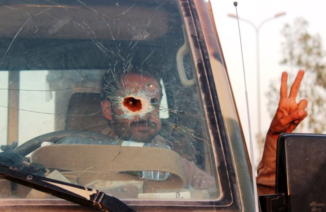 A Yemeni soldier, pictured through a vehicle's windscreen, which was damaged by a bullet, gestures out of the window, in Marib, Yemen October 15, 2015. Marib is a city that is heavily armed even by the standards of Yemen, where the ready availability of weapons helped start civil war and is now preventing anyone coming out on top. (Photo by Angus McDowall/Reuters)