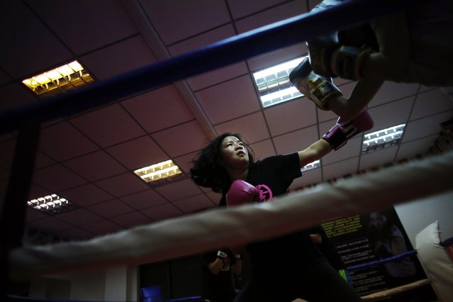 A woman punches during a boxing class at Princess Women's Boxing Club in Shanghai December 3, 2014. (Photo by Carlos Barria/Reuters)