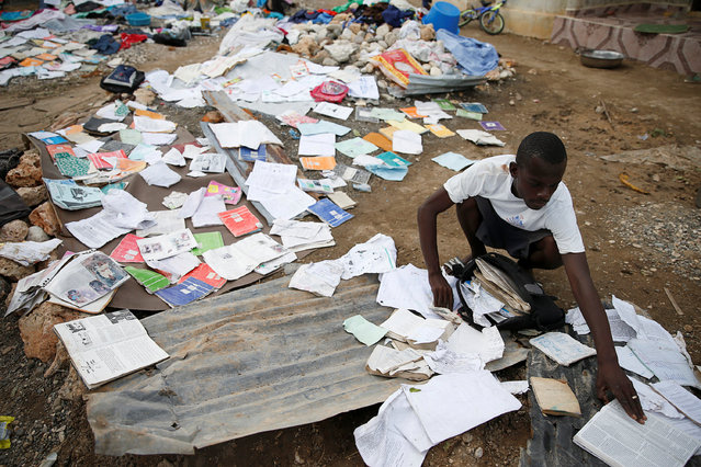 A man grabs papers from the floor after Hurricane Matthew passes Jeremie, Haiti, October 7, 2016. (Photo by Carlos Garcia Rawlins/Reuters)