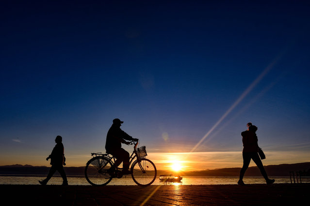 People pass by a riverside at sunset in Ohrid, North Macedonia on October 22, 2020. (Photo by Chine Nouvelle/SIPA Press/Rex Features/Shutterstock)