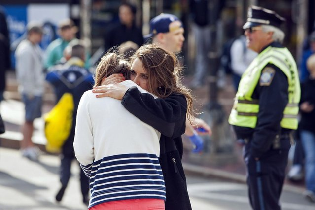 A woman comforts another, who appears to have suffered an injury to her hand, after explosions interrupted the 117th Boston Marathon in Boston, Massachusetts April 15, 2013. (Photo by Dominick Reuter/Reuters)