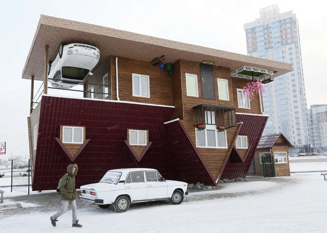 A man passes a house built upside-down in Russia's Siberian city of Krasnoyarsk, December 14, 2014. The house was constructed as an attraction for local residents and tourists. (Photo by Ilya Naymushin/Reuters)
