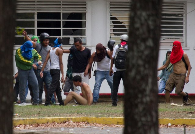 In this April 3, 2014 file photo, government supporters beat a naked opposition student as he's forced to sit on the ground inside of the Central University of Venezuela, UCV, during an anti-government protest in Caracas, Venezuela. Students attempted to march from the university to protest the country's deteriorating economy, but hundreds of riot police prevented them from leaving campus, deploying tear gas and flash-bang grenades. (Photo by Fernando Llano/AP Photo)