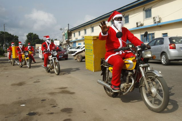 Jumia delivery men dressed as Santa Claus drive their motorcycles to deliver goods to customers in Abidjan December 18, 2014. (Photo by Luc Gnago/Reuters)