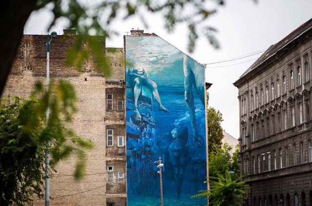 """An urban artwork, a mural painted on a firewall of a residental building next to the parking lot of the Semmelweis University in the Ulloi Street in Budapest, Hungary, October 3, 2016. The giant mural, which covers 240-square-meter was created by Polish street artists Michal """"Sepe"""" Wrega and Daniel """"Chazme"""" Kalinowski during the annual month-long mural-painting event, known as Colorful City Festival. (Photo by Balazs Mohai/AP Photo)"""