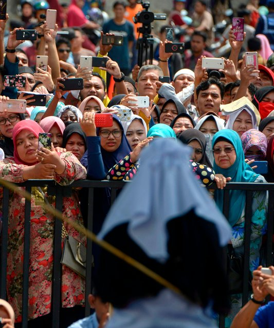 Onlookers hold up smartphones as they witness a public flogging in front of a mosque in the provincial capital Banda Aceh on April 20, 2018. (Photo by Chaideer Mahyuddin/AFP Photo)