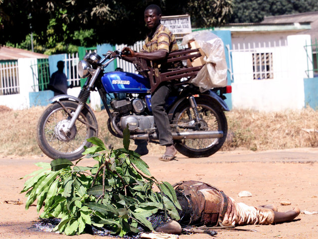 Nigerian men on A motorcycle drive by a body in the northern city of Kaduna on November 22, 2002, after rioting youths torched houses and churches. (Photo by Juda Ngwenya/Reuters)