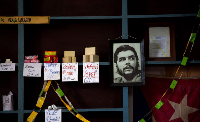 """In this October 22, 2013 file photo, a framed image of Argentine born Cuban revolutionary hero, Ernesto """"Che"""" Guevara, hangs on a shelf at a state-run food store, with products tagged in ordinary Cuban pesos in Havana, Cuba. On April 19, 2018 Raul Castro will step down as president after a decade in office. The transition to a group of leaders from the """"lost generation"""" will require potentially painful reforms, like the elimination of a dual-currency system that has created damaging economic distortions. (Photo by Ramon Espinosa/AP Photo)"""