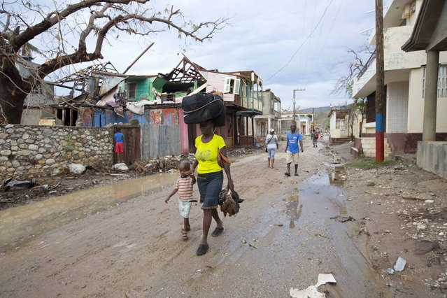 In this Tuesday, October 18, 2016 photo, a mother and her child walk to a nearby bus stop with their personal belongings, in Port-a-Piment, a district of Les Cayes, Haiti, where they will board a bus to the capital to stay with relatives, because Hurricane Matthew destroyed their home. (Photo by Dieu Nalio Chery/AP Photo)