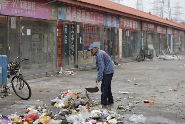 A man clears rubbish at a closed market near the Central Business District (CBD) area, outside a construction site in Beijing, China, October 26, 2015. A slowdown in China is forcing multinational companies to treat the world's second-biggest economy more like a developed market, turning away from a headlong dash for growth to focus on premium businesses, or improving productivity by investing in staff. Picture taken on October 26, 2015. (Photo by Jason Lee/Reuters)