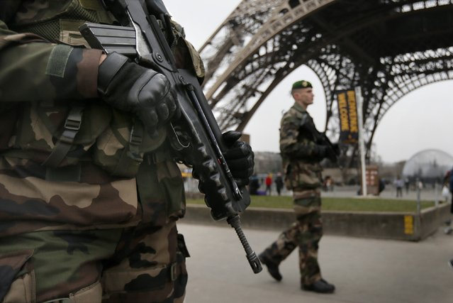 "French soldiers patrol near the Eiffel Tower in Paris as part of the highest level of ""Vigipirate"" security plan after a shooting at the Paris offices of Charlie Hebdo January 7, 2015. Gunmen stormed the Paris offices of the weekly satirical magazine Charlie Hebdo, renowned for lampooning radical Islam, killing at least 12 people, including two police officers in the worst militant attack on French soil in recent decades. (Photo by Gonzalo Fuentes/Reuters)"