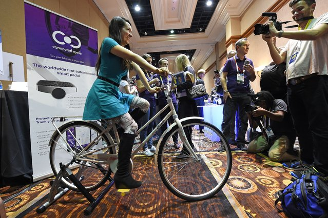 An attendee rides a bicycle equipped with a yellow Connected Cycle smart pedal,  during media preview event at the 2015 Consumer Electronics Show, January 4, 2015 in Las Vegas, Nevada. The Connected Cycle pedal is equipped with GPS and GPRS sensors that are powered by cycling and can help locate a bicycle in case of theft. When the pedal moves sensors track the users activity tracking training information by recording speed, route, incline, and calories burned. (Photo by Robyn Beck/AFP Photo)