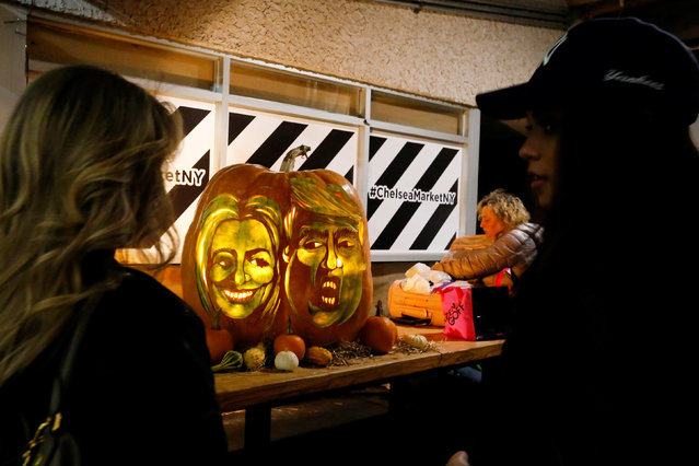 People take a look of a giant pumpkin created by Master Carver Hugh McMahon with the faces of 2016 Democratic nominee Hillary Clinton and Republican presidential nominee Donald Trump at Chelsea Market in New York, U.S., October 28, 2016. (Photo by Eduardo Munoz/Reuters)