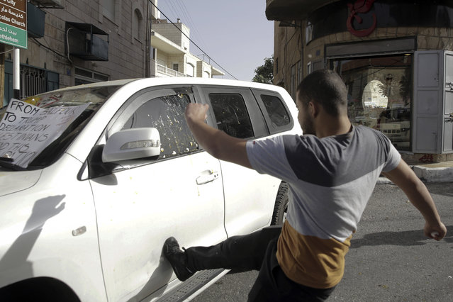 A Palestinian activist kicks a vehicle of a delegation from the U.S. Embassy in Jerusalem as they arrive for a meeting in Beit Jala, West Bank, Monday, May 21, 2018. A small group of Palestinian protesters in the West Bank has pelted an American diplomatic vehicle with eggs to protest the recent move of the U.S. Embassy to Jerusalem. (Photo by Mahmoud Illean/AP Photo)