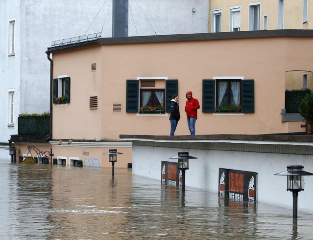 People stand on the roof of a building and look at a flooded street in the centre of the Bavarian town of Passau, about 200 km (124 miles) north-east of Munich June 3, 2013. Torrential rain in the south and south-east of Germany caused heavy flooding over the weekend, forcing people to evacuate their homes. (Photo by Michaela Rehle/Reuters)