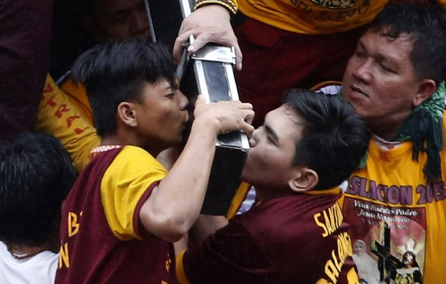 Devotees kiss the Black Nazarene at the start of an annual procession in Manila, January 9, 2015. (Photo by Erik De Castro/Reuters)
