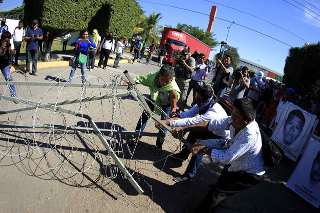 Activists and relatives of the 43 missing trainee teachers from Ayotzinapa's teacher training college pull a barbed wire during a demonstration at the military zone of the 27th infantry battalion in Iguala, Guerrero, January 12, 2015. (Photo by Jorge Dan Lopez/Reuters)