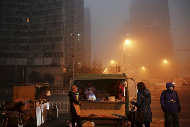 Street vendors prepare food for commuters on an extremely polluted morning as hazardous, choking smog continues to blanket Beijing, China December 1, 2015. (Photo by Damir Sagolj/Reuters)