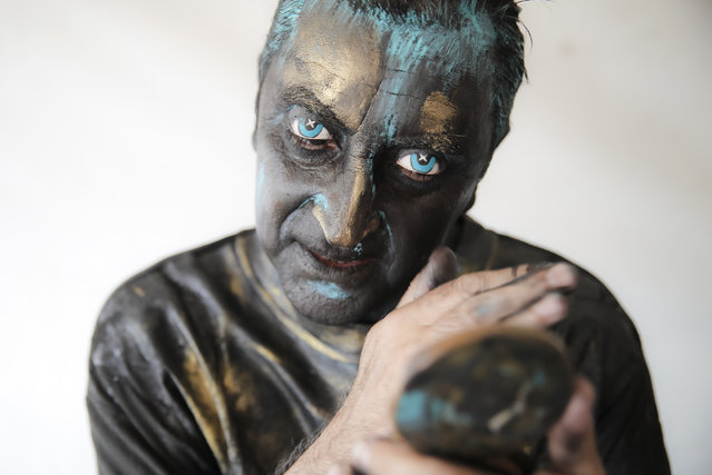 """In this Sunday, May 27, 2018, photograph, Portuguese artist Antonio Santos checks his make-up during the Living Statues International Festival, in Bucharest, Romania. Up to thirty thousand people enjoyed a week of street performances by reputed artists from eight countries in the """"largest European festival of the genre"""". (Photo by Vadim Ghirda/AP Photo)"""