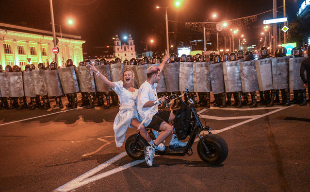 Protesters ride an electric bike in front of police during a protest after polling stations closed at the presidential elections in Minsk, Belarus, 09 August 2020. Five candidates are contesting for the presidential seat, including the incumbent president Lukashenko. (Photo by Tatyana Zenkovich/EPA/EFE)