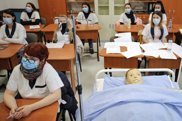 Students of a nursing school sit in a classroom during a visit by local administration officials, on the opening day of schools and kindergartens in Bucharest, Romania, Monday, February 8, 2021. Romania re-opened schools after one of the longest periods of interruption due to the COVID-19 pandemic among European Union countries with up to 2.1 million children going back into schools on Monday and 780 thousand continuing the online education. (Photo by Vadim Ghirda/AP Photo)