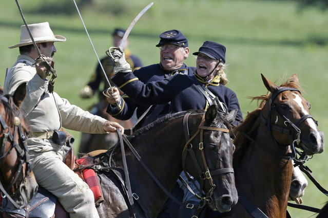 Reenactors demonstrate a cavalry battle during ongoing activities commemorating the 150th anniversary of the Battle of Gettysburg, Saturday, June 29, 2013, at Bushey Farm in Gettysburg, Pa. Union forces turned away a Confederate advance in the pivotal battle of the Civil War fought July 1-3, 1863, which was also the war's bloodiest conflict with more than 51,000 casualties. (Photo by Matt Rourke/AP Photo)