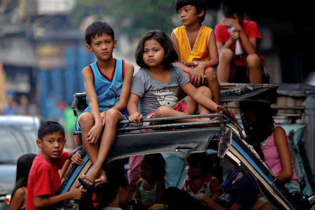 Children watch as policemen investigate near the body of a woman killed by unknown gunmen at the market in a port area of Manila, Philippines October 28, 2016. (Photo by Damir Sagolj/Reuters)