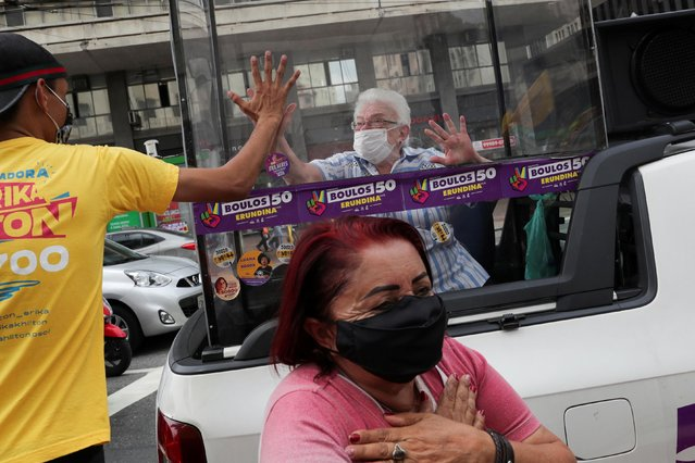 """Luiza Erundina, 85, leftist Guilherme Boulos's candidate for vice-mayor, holds her hand to a man's from inside the """"cata voto"""" (Vote Catcher), a car with a plastic booth to protect herself from the coronavirus disease (COVID-19) during the campaign in Sao Paulo, Brazil on November 13, 2020. (Photo by Amanda Perobelli/Reuters)"""