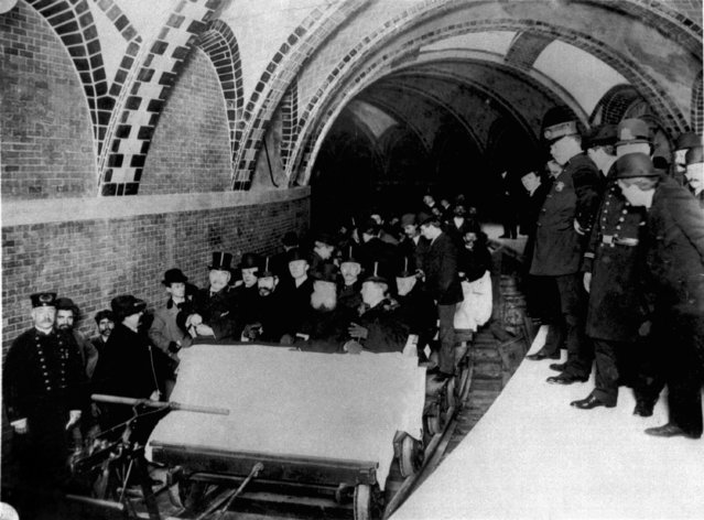 This group of financiers and city officials get a tour of New York City's first subway in January 1904 while the city's policemen stood by on the platform at City Hall Station.  Seated toward the front of the ceremonial flat car are Alexander Orr, August Belmont, John B. McDonald, and Mayor George B. McClellen. (Photo by AP Photo/NYC Transit Authority)