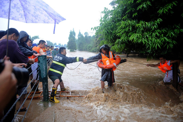 Firefighters use a rope to help a woman (C) walk across floodwaters after heavy rainfalls hit Dujiangyan, Sichuan province July 9, 2013. At least one person died and 15 others were missing in southwest China's Sichuan Province as of Tuesday evening after severe rainstorms battered the region, including some quake-stricken areas, Xinhua News Agency reported. (Photo by Reuters/China Daily)