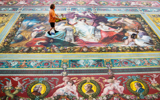 A conservator walks over a curtain on July 24, 2013 in the painting workshop of the Semper Opera House in Dresden, Germany. The curtain was reconstructed in 1984 after the original design by Ferdinand Keller and now needs to be cleaned after almost 30 years. The original from 1878 was burned in the bombing of Dresden on February 13,1945. (Photo by Hannibal Hanschke/AFP Photo/DPA)