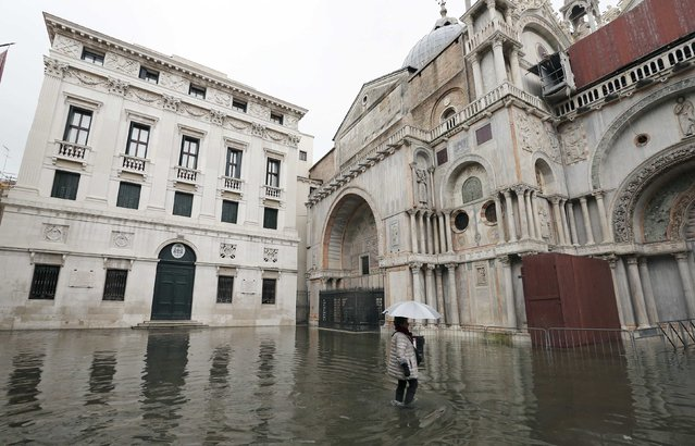 A woman walks through the flooded St. Mark's Square during a period of seasonal high water and on the first day of carnival, in Venice February 1, 2015. (Photo by Stefano Rellandini/Reuters)