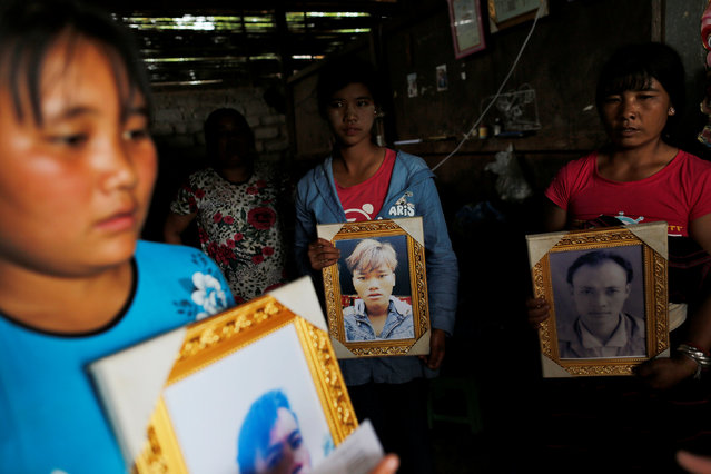 Women pose while holding portraits of their killed relatives (L-R) Aik Sai, Aik Maung and Aik Lort after their bodies were found in a grave last June at Mong Yaw village in Lashio, Myanmar July 10, 2016. (Photo by Soe Zeya Tun/Reuters)