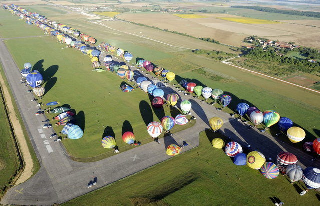 "Over 390 hot air-balloons prepare to take off in Chambley-Bussieres, eastern France on Aug. 1, 2013 to set a world record of collective taking-off during the yearly event ""Lorraine Mondial air ballons"", an international air-balloon meeting. (Photo by Jean Christophe Verhaegen/AP Photo)"