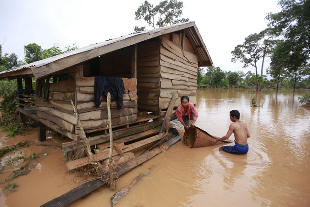 Kongvilay Inthavong and his wife Thongla clean up their house as the floodwaters start to recede i in Sanamxay district, Attapeu province, Laos on Thursday, July 26, 2018. An estimated 25,000 people are being evacuated from a northern Cambodian province following extensive flooding due to the collapse of a massive hydropower dam in neighboring Laos. Authorities in Stung Treng province are attempting to evacuate towns and villages downstream from the dam, which has caused waters to rise above 12 meters (39 feet) in places, according to Cambodia's state news agency. The collapse of the hydropower dam has already left at least 26 people dead and another 6,000 homeless in southern Laos, the worst disaster faced by the small Southeast Asian country in decades, according to Laotian Prime Minister Thongloun Sisoulith. (Photo by Hau Dinh/AP Photo)