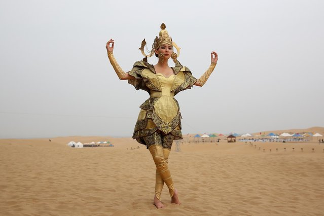 A model in Mongolia costumes poses for photos in Xiangshawan Desert, also called Sounding Sand Desert on July 21, 2013 in Ordos of Inner Mongolia Autonomous Region, China. Xiangshawan is China's famous tourist resort in the desert. It is located along the middle section of Kubuqi Desert on the south tip of Dalate League under Ordos City. Sliding down from the 110-metre-high, 45-degree sand hill, running a course of 200 metres, the sands produce the sound of automobile engines, a natural phenomenon that nobody can explain. (Photo by Feng Li/Getty Images)