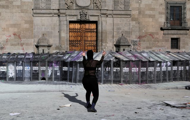 A woman gestures in front of police officers during a protest in support of Victoria Salazar, a Salvadoran woman who died after a Mexican female police officer was seen in a video kneeling on her back, in Mexico City, Mexico on April 2, 2021. (Photo by Raquel Cunha/Reuters)
