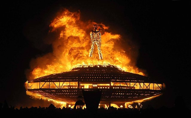 """The """"Man"""" burns on the Black Rock Desert at Burning Man near Gerlach, Nev. on August 31, 2013.  U.S. Bureau of Land Management spokesman Mark Turney said Saturday more than 61,000 people have turned out so far for the weekend Burning Man outdoor art and music festival in the Black Rock Desert of northern Nevada. (Photo by Andy Barron/AP Photo/Reno Gazette-Journal)"""