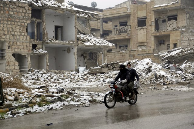 Men ride a motorbike past damaged buildings covered with snow in the rebel-controlled area of Maaret al-Numan town in Idlib province, Syria, January 5, 2016. (Photo by Khalil Ashawi/Reuters)