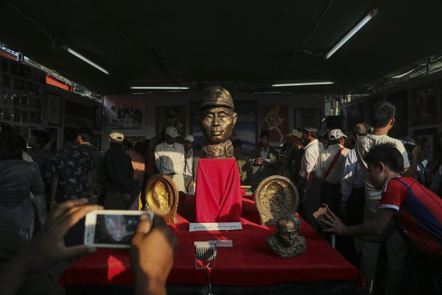 People gather near a bust of independence hero General Aung San, to mark the eve of his 100th birthday anniversary, in his home town Natmauk, Magway division central Myanmar, February 12, 2015. (Photo by Soe Zeya Tun/Reuters)