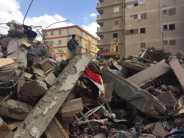 Emergency workers sift through the rubble of a collapsed apartment building in the el-Salam neighborhood, Saturday, March 27, 2021, in Cairo, Egypt. (Photo by Mohamed Salah/AP Photo)