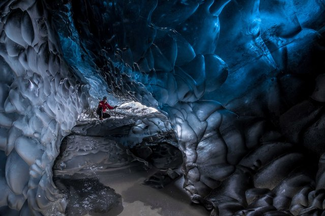Stunning images have revealed ice-cool British tourists chilling out inside Europe's largest glacier – despite being at risk of flooding. The spectacular collection of images show the explorers braving the freezing temperatures to climb, photograph and even abseil down the inside of the icy cliff sides. Another image shows one visitor on his knees appearing to pray next to a water fall of melted ice. Other glistening shots show an adventurer trying to keep warm by a fire whose flames dance beautifully against the glossy roof. More shots show the caves sparkling like crystal with one ice formation appearing to resemble bubble wrap. In one picture, a brave tourist stands at the edge of a river flowing through the centre of the frosty caves. (Photo by Einar Runar Sigurdsson/Mediadrumworld.com)