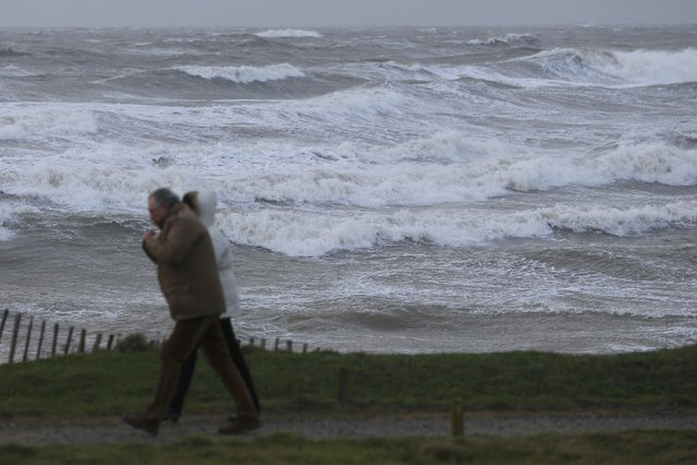A couple walks near the beach as strong winds and high waves from a winter storm are seen at the Saint Gildas Point in Prefailles, France as stormy weather hits the French Atlanitic coast January 11, 2016. (Photo by Stephane Mahe/Reuters)