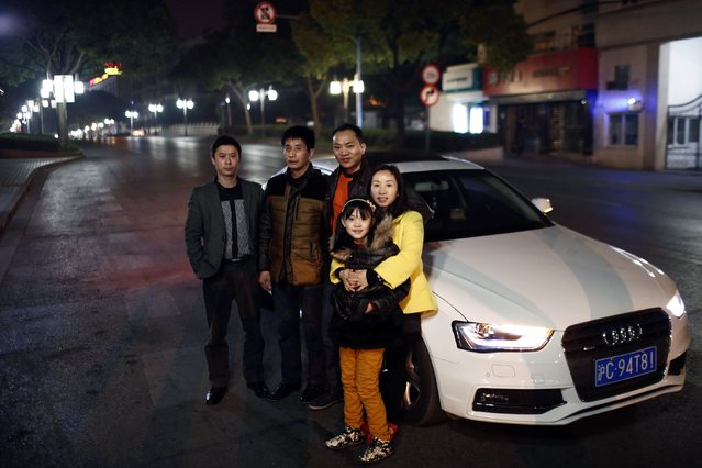 Wang Wenfang (2nd R), his wife Hu Haiyan (R), daughter Wang Yuyuan, father-in-law Hu Zhengyun (2nd L) and colleague Zhao Bin (L) pose for a portrait as they leave Shanghai on a car for the upcoming Chinese New Year February 12, 2015. Wang and his family travelled to Sichuan province by car to spend Chinese New Year with the rest of his family. (Photo by Carlos Barria/Reuters)