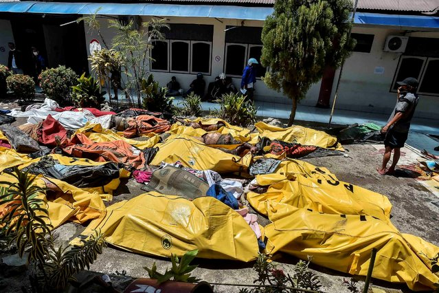 A man examines earthquake and tsunami victims who were placed outside the Bhayangkara Hospital after a quake in Palu, Central Sulawesi, Indonesia September 30, 2018  in this photo taken by Antara Foto. (Photo by Muhammad Adimaja/Reuters/Antara Foto)