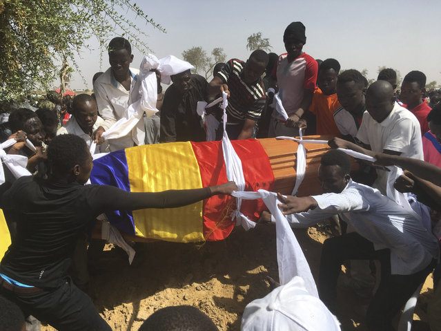 Mourners lower the coffin of one of the victims of protest who was killed this week during his funeral at a cemetery in N'Djamena, Chad, Saturday, May 1, 2021. Hundreds of chanting mourners carrying Chadian flags gathered Saturday to bury victims who were shot dead earlier this week amid demonstrations against the country's new military government. (Photo by Sunday Alamba/AP Photo)