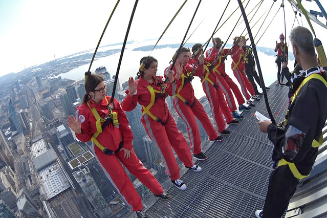 "Six new Canadians take their oath of citizenship while harnessed on the CN Tower's ""Edgewalk"" 356 metres (1,168 feet) above Toronto, Ontario, Canada in a still image from video October 9, 2018. (Photo by CN Tower/Handout via Reuters)"