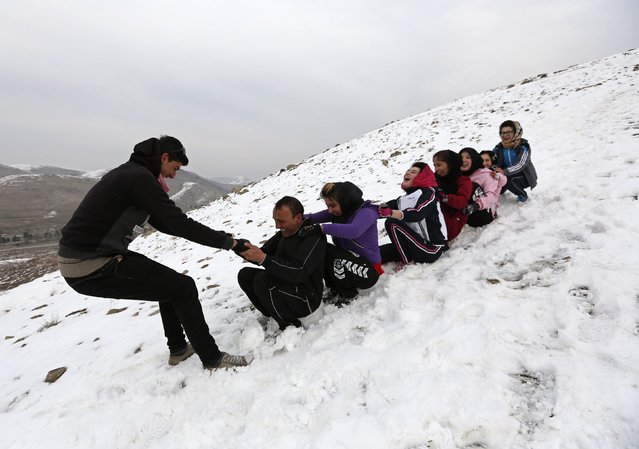 Members of Afghanistan's Women's National Cycling Team slide down a hill after exercises on a snowy mountain in Qargha on the outskirts of Kabul March  9, 2015. (Photo by Mohammad Ismail/Reuters)