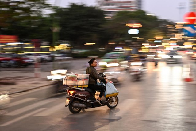 A woman rides her scooter against the traffic along a street in Hanoi on March 23, 2021. (Photo by Manan Vatsyayana/AFP Photo)